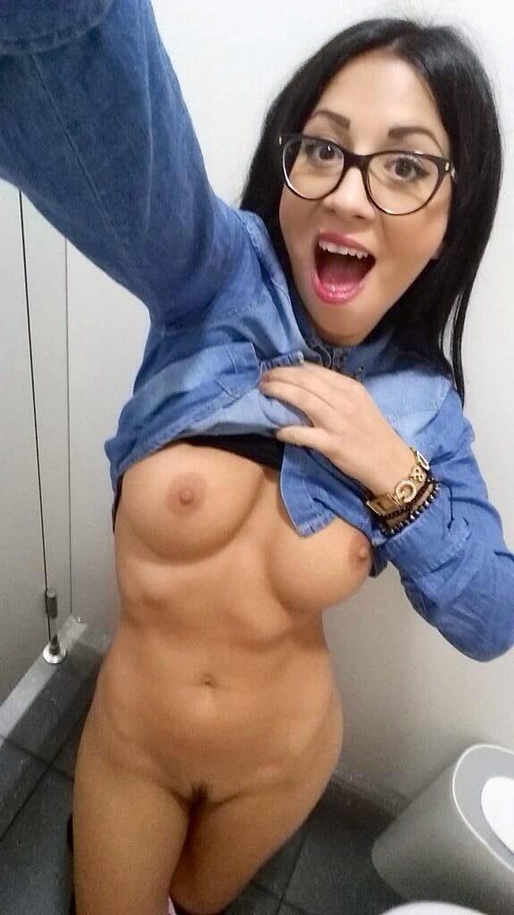 Селфи девушки в очках с голой грудью в кабинке туалета