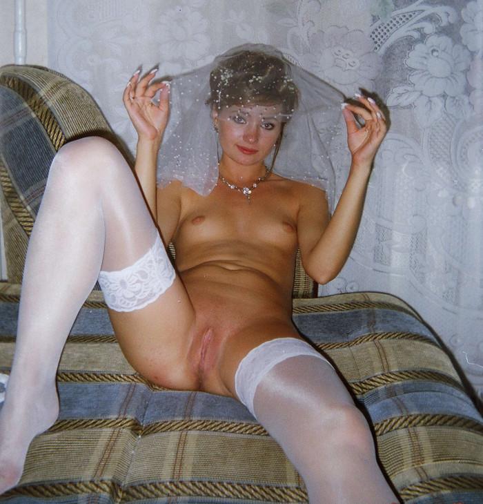 Невеста в фате и чулках лежит на диване, показывая свою киску